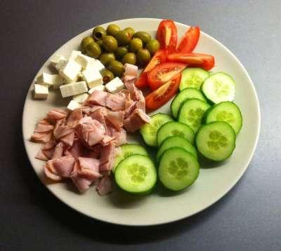 Mat, en tallrik med gurka, tomat, fetaost, skinka och oliver. God mat är lycka, är jag ensam ska det vara enkelt. Oberörd av julen.