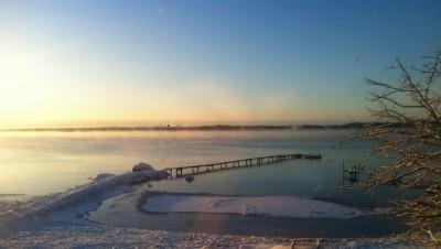 Vintrigt lantställe, hav och brygga, snö