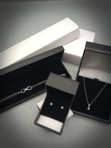 a selection of fine sterling silver jewellery on a grey/silver background with a slight black vinagette