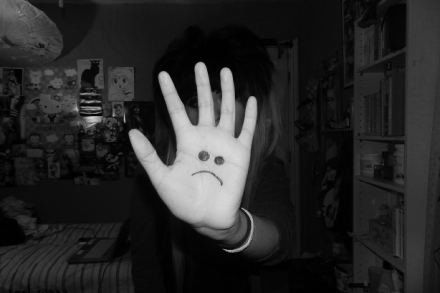 Ung kvinne står på et jenteværelse og holder hånden foran ansiktet. På ansiktet er det tegnet et surt fjes.