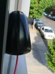 En luftsensor henger i en vinduskarm over bakkeplan.