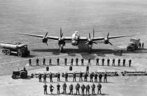 The personnel required to keep one Avro Lancaster flying on operations, taken at Scampton, Lincolnshire. Front row (left to right); flying control officer, WAAF parachute packer, meteorological officer, seven aircrew (pilot and captain, navigator and observer, air bomber, flight engineer, wireless operator/air gunner and two air gunners): second row, twelve flight maintenance crew (left to right; n.c.o. fitter, flight maintenance mechanic, n.c.o. fitter, five flight maintenance mechanics, electrical mechanic, instrument repairer, and two radio mechanics): third row, bombing up team; WAAF tractor driver with a bomb train of 16 Small Bomb Containers (SBC), each loaded with 236 x 4-lb No. 15 incendiaries and, behind, three bombing-up crew: fourth row, seventeen ground servicing crew (left to right; corporal mechanic, four aircraft mechanics, engineer officer, fitter/armourer, three armourers, radio mechanic, two instrument repairers, three bomb handlers, machine gunbelt fitter): back row (left to right); AEC Matador petrol tender and two crew, Avro Lancaster B Mark I heavy bomber, mobile workshop and three crew.