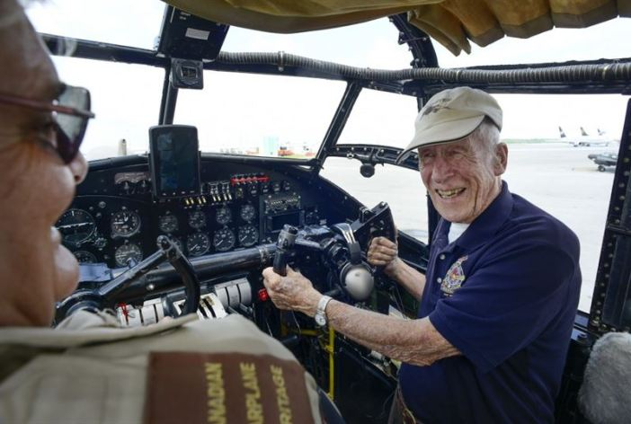 Former Lancaster pilot Jack Finan stands at the controls of the Canadian Warplane Heritage Museum's Lancaster as he talks to pilot Dave Rohrer. Finan took a ride in the Lanc on Saturday. It had been 50 years since he had stepped in one. (Credits: The Hamilton Spectator)