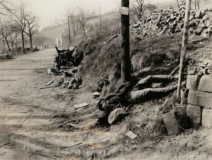 Dead German soldiers lie where they fell after artillery worked over this German town during the Seventh Army breakthrough.