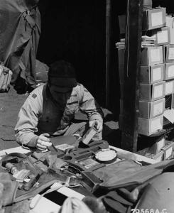 Two years after surviving his accident at Midway Atoll, Capt. Ray L. Obenshain, Assistant Operations Officer of Fresno, California, checks his jungle pack at the 47th Fighter Squadron, 15th Fighter Group base on Iwo Jima, Bonin Islands. (Credits: Mark Stevens, 7th Fighter Command Association)