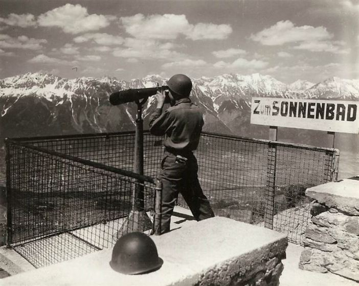 Yanks go on a special service tour to Tyrol Mountains resort. Yank looks through the telescope on top of the Tyrol mountain. From here can be seen Innsbruck, Austria and the Brenner Pass.