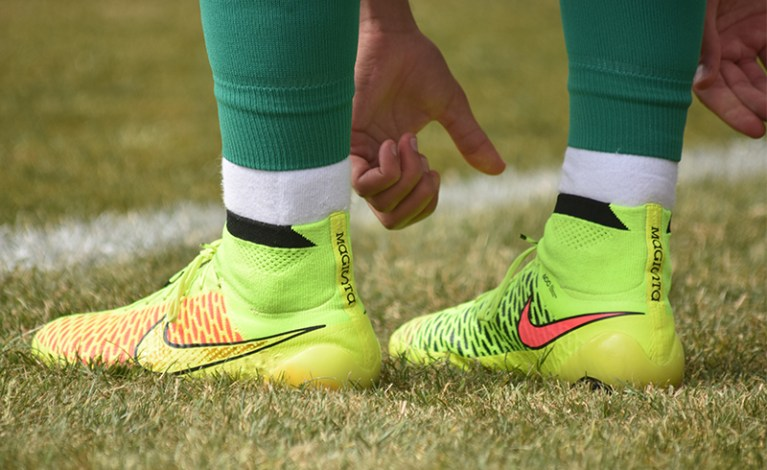 A pair of yellow and lime green football boots. The player wearing them is stood on the touchline. Their hands are visible as they reach down to tie their shoelaces.