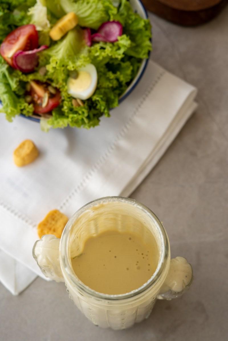 na parte inferior um pote de vidro com o cremoso molho para saladas de iogurte e tahine, na parte superior um bowl com salada de folhas verdes