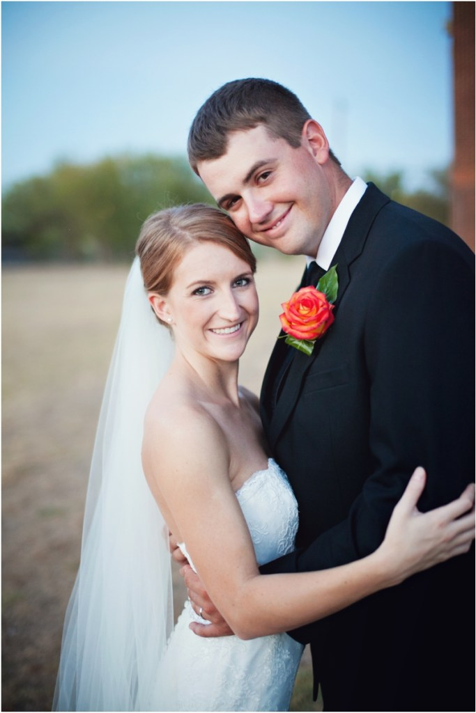 Wedding day portrait of bride and groom with veil and boutonniere