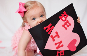 baby girl in pink dress with be mine sign for valentine's day photo