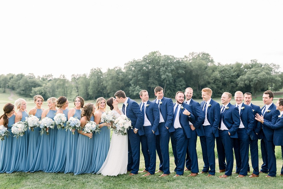 Arielle Peters Photography | Bride and groom kissing with wedding party at The Blue Heron at Blackthorn in South Bend, Indiana on wedding day.