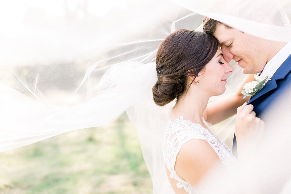 Arielle Peters Photography | Bride and groom kissing under her veil outside at The Blue Heron at Blackthorn in South Bend, Indiana on wedding day.