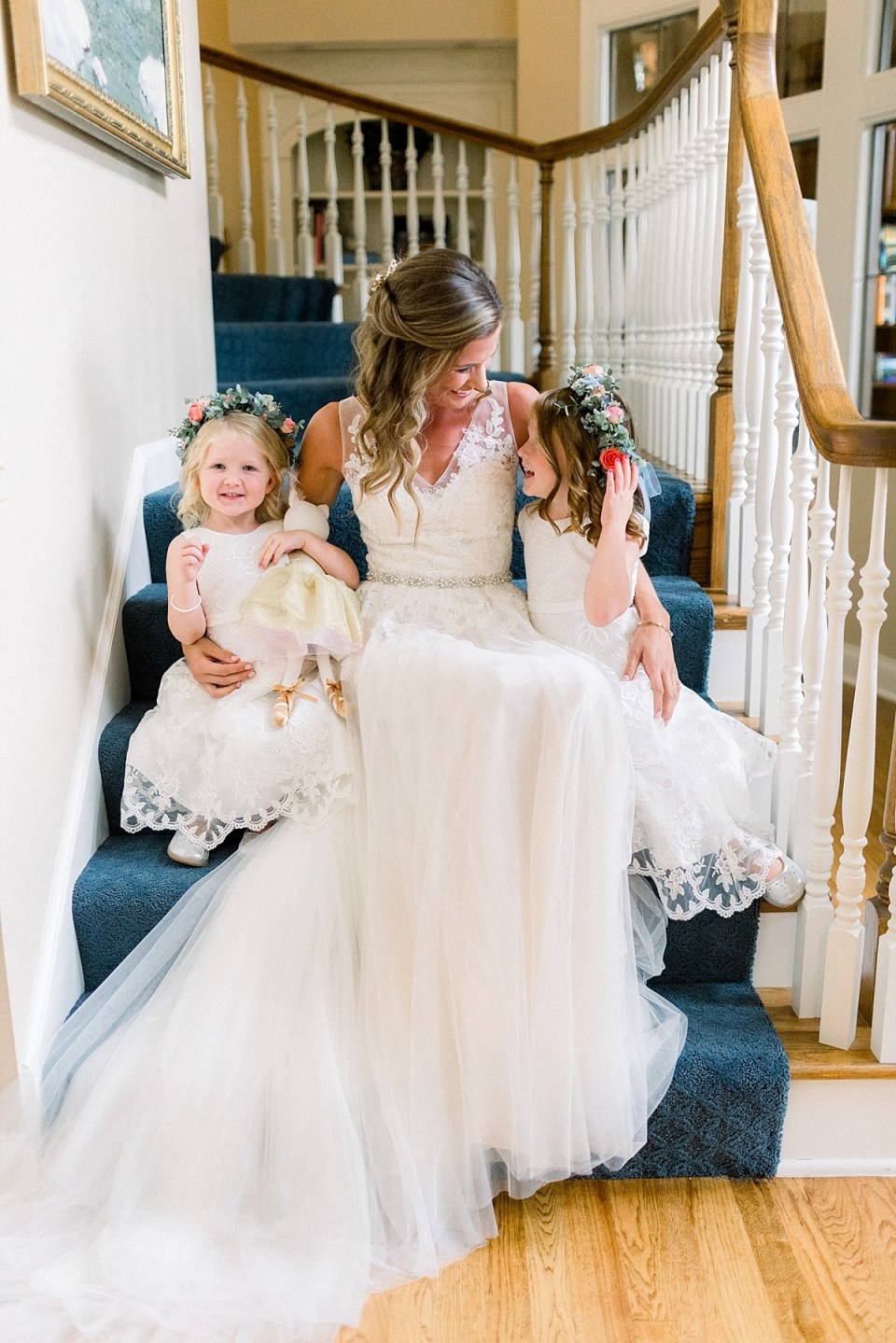 Arielle Peters Photography | Bride sitting with flower girls on stairs at Sycamore Hills Golf Club in Fort Wayne, Indiana on wedding day.