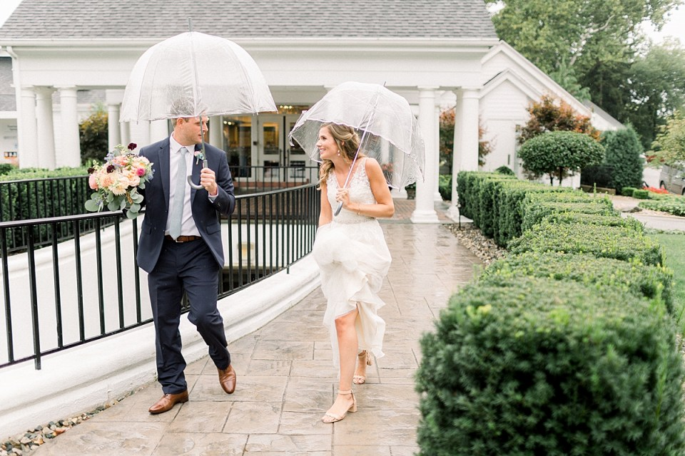 Arielle Peters Photography | Bride and groom walking outside in rain on wedding day at Sycamore Hills Golf Club in Fort Wayne, Indiana.