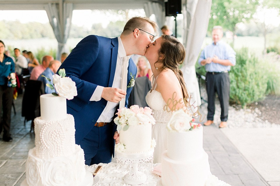 Arielle Peters Photography | Bride and groom kissing by the cake at the wedding reception at The Bridgewater Club in Carmel, Indiana on wedding day.