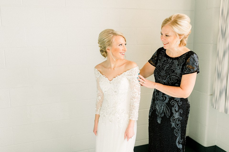 Arielle Peters Photography | Mother of the bride smiling at the bride in her dress on her wedding day.