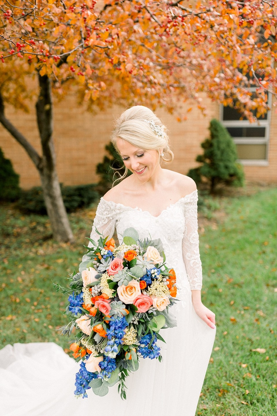 Arielle Peters Photography | Bride smiling with her bouquet outside on fall wedding day.