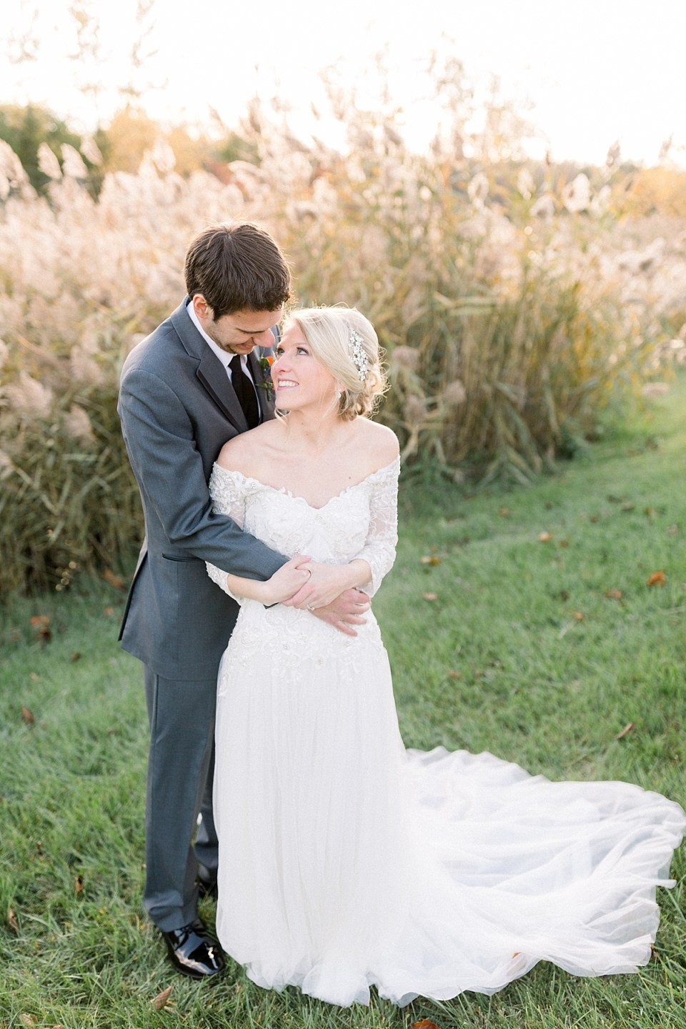 Arielle Peters Photography | Bride and groom smiling at each other outside in a field on fall wedding day.