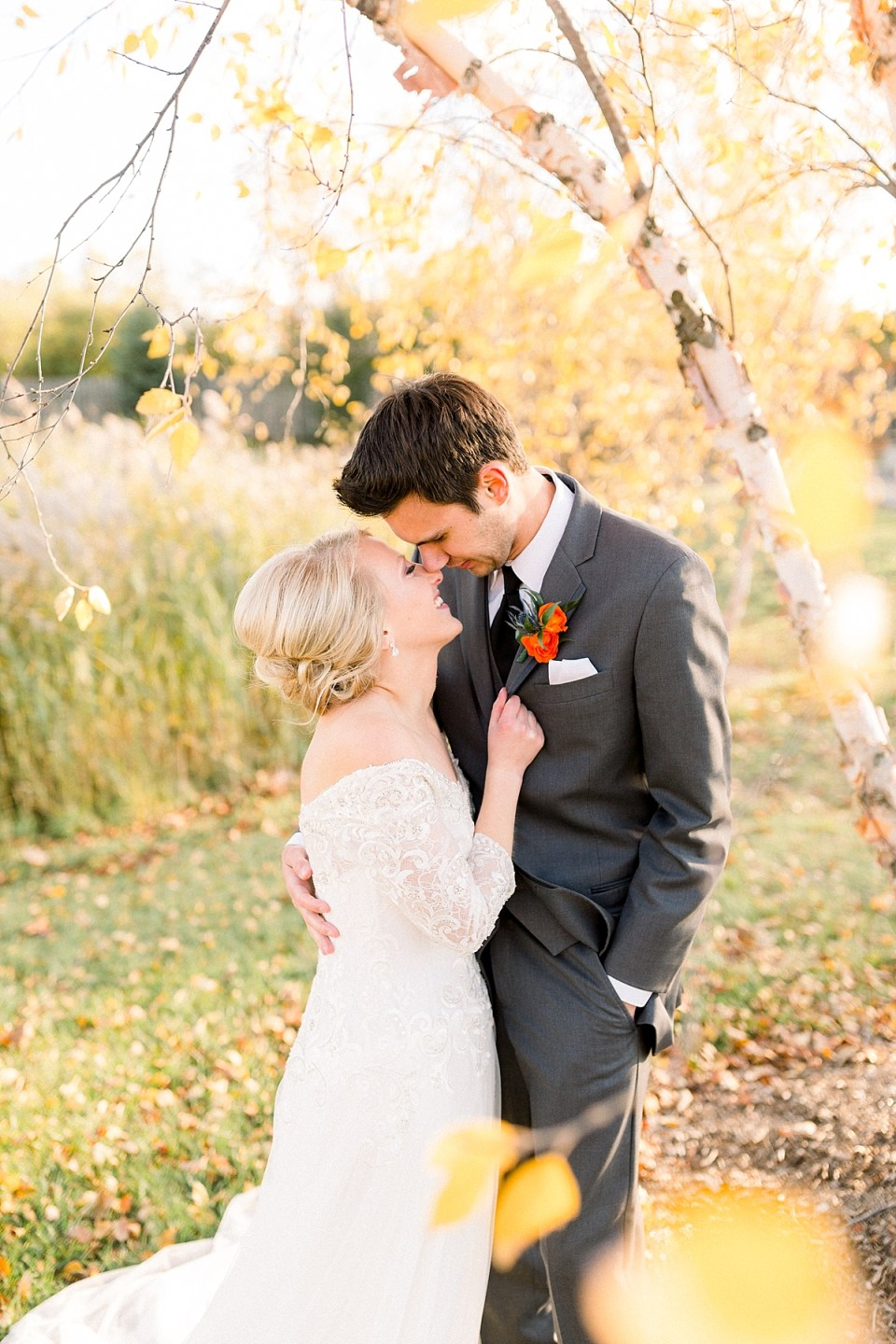 Arielle Peters Photography | Bride and groom smiling at each other outside under trees on fall wedding day.