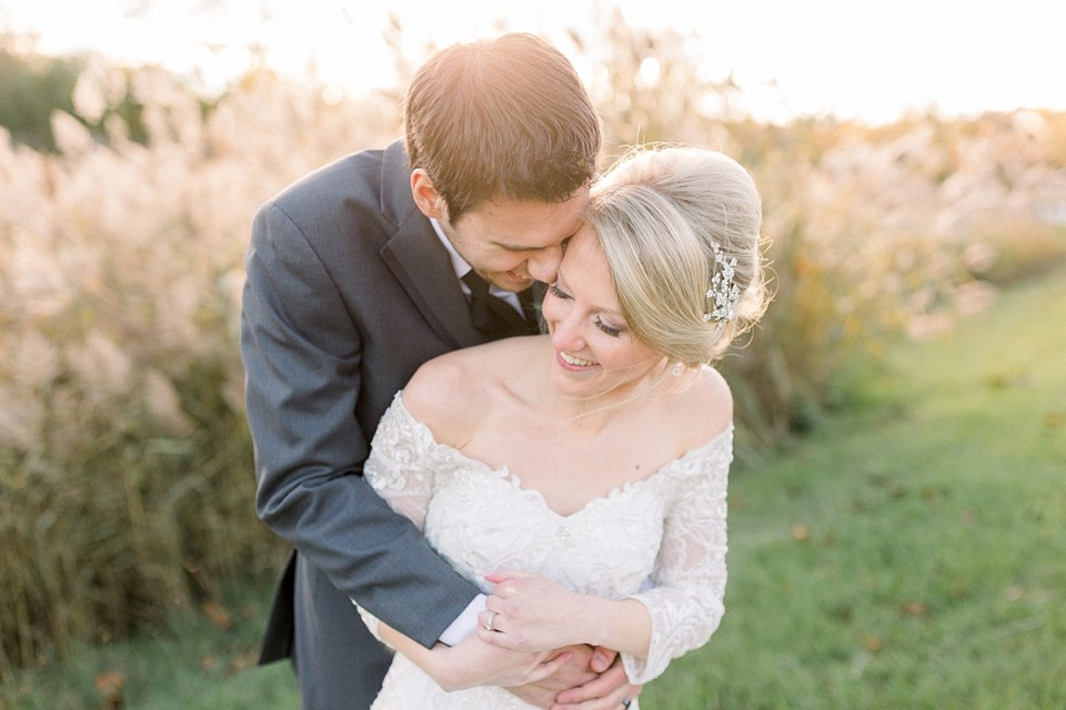 Arielle Peters Photography | Groom holding the bride in his arms outside in a field on fall wedding day.
