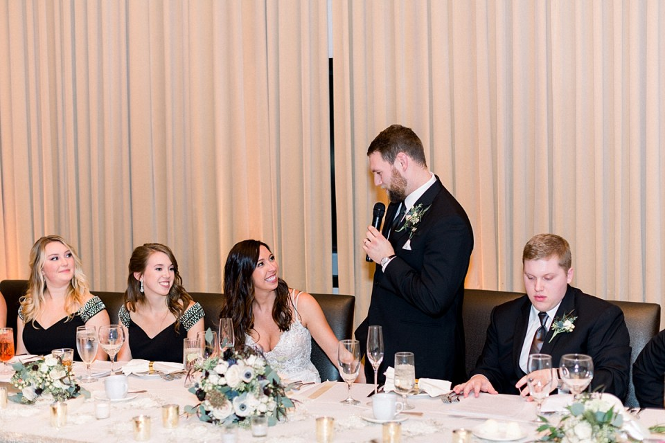 Arielle Peters Photography | Groom speaking to the bride at head table at wedding reception.