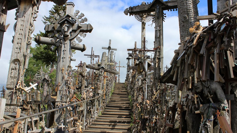 A small wooden path between lines of crosses and crucifixes.