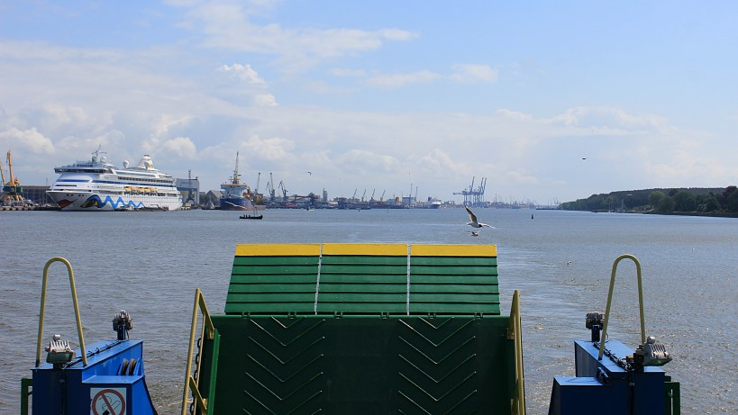 The back of the ferry to Curonian Spit with a green car ramp and a cruise ship in the background.