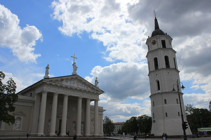The Cathedral of Vilnius with white pillars, a tower in front and dramatic clouds in the background.