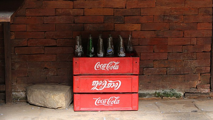 Coca-Cola containers and empty glass bottles in Durbar Square of Kathmandu by a brick wall.
