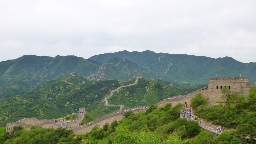The Great Wall of China in Badaling with mountains and cloudy sky in the background.