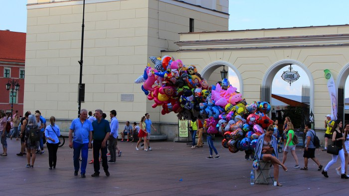 A girl selling balloons that blow in the wind in the Old Town of Warsaw.