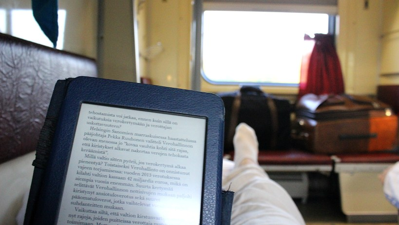 Reading Amazon Kindle Paperwhite when traveling on a sleeper car of a train. A good way to waste time during long train journeys.