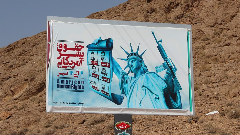 "American Human Rights, an Iranian propaganda billboard on the side of the road. The Statue of Liberty holds a gun in one hand and pictures of the ""nuclear martyrs"" of Iran in other."