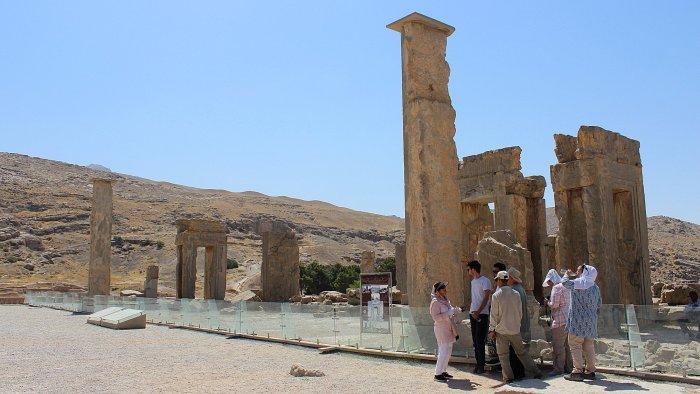Tourist group taking shade behind a pillar at the ruins of Persepolis.