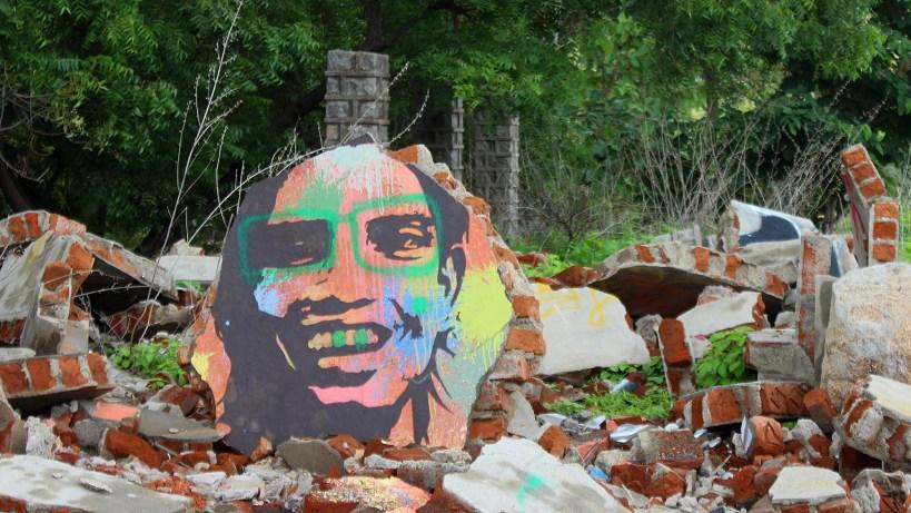 A colorful graffiti of a smiling man on a piece of concrete in Virupapur Gaddi.