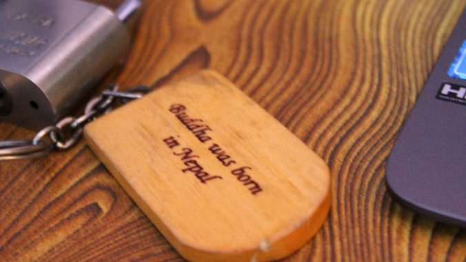 """A wooden keychain for a guestroom key saying """"Buddha was born in Nepal""""."""
