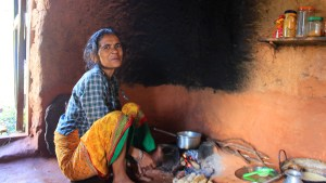 A Nepalese woman cooking food in a traditional ground stove.
