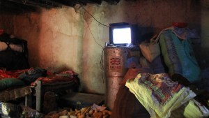 A dark Nepalese village room with a small television and corncobs on the floor.