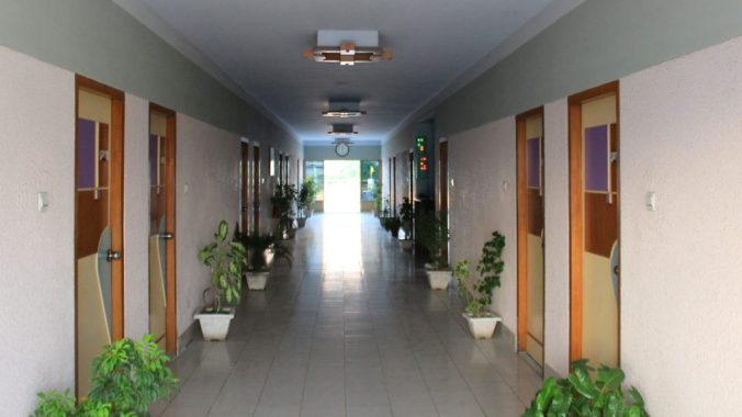 An empty hotel corridor with closed doors and light coming from the back door in Khulna, Bangladesh.