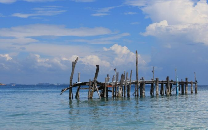 An old wooden dock out in the ocean with no connection to the coast in the island of Koh Samet, Thailand.
