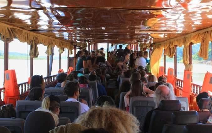 Inside the slow boat from Luang Prabang to Huay Xai, with passengers sitting on their chairs.
