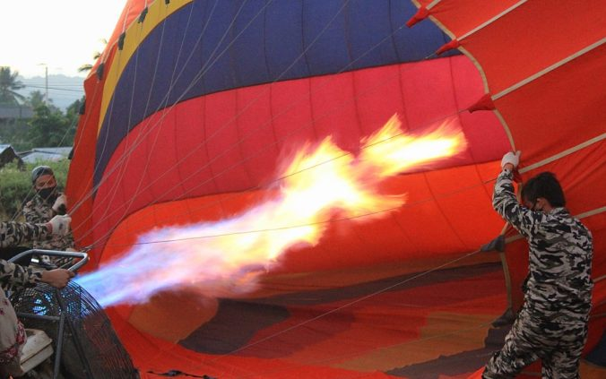 Inflating a hot air balloon in Vang Vien, Laos with a giant flame.