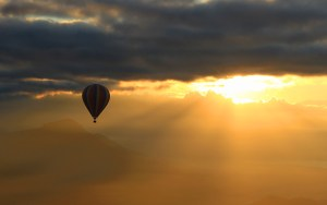 Hot air ballooning in Vang Vieng, Laos. A hot air balloon flying against the sunrise in the background.