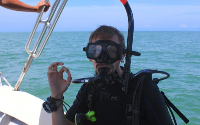 Diver giving the OK signal on the boat.