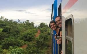 Backpackers peeking out of the open door of the TAZARA train from Tanzania to Zambia.