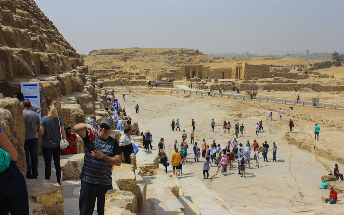 Tourists climbing on the Great Pyramids of Giza in 2018. Visiting Cairo, Egypt in 2018.