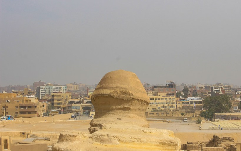 The Sphinx of Giza from behind with Cairo and smog in the background.