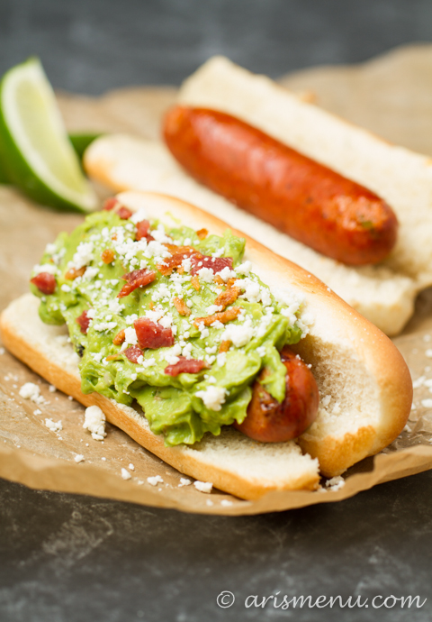 Spicy Bacon Guacamole Dogs: Spicy grilled hot dogs smothered with roasted jalapeno & garlic bacon guacamole + cotija cheese