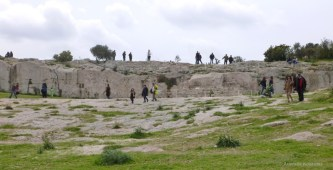 Athenians strolling in front of the Bema of Pnyx.