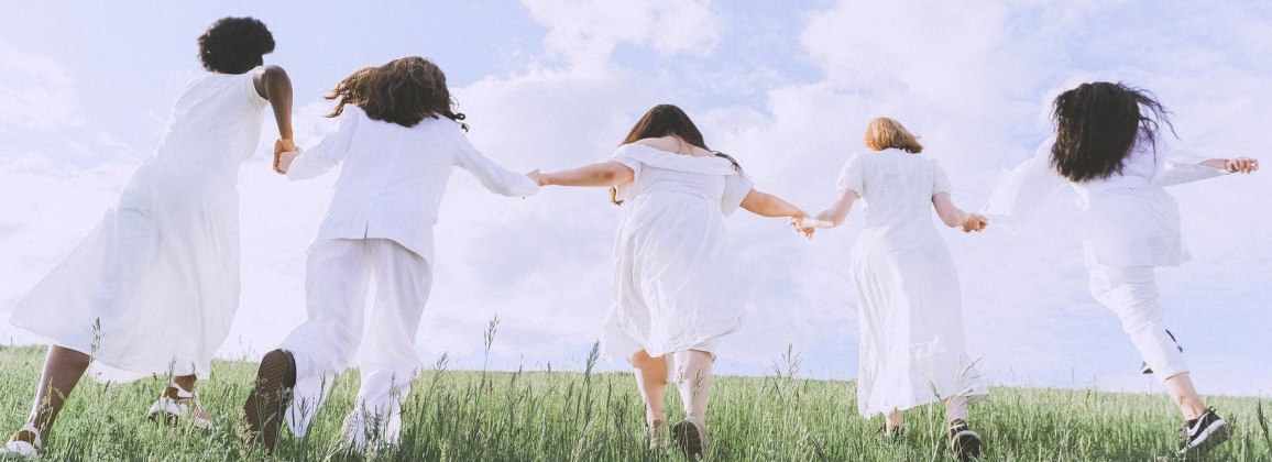Five young girls running in a field